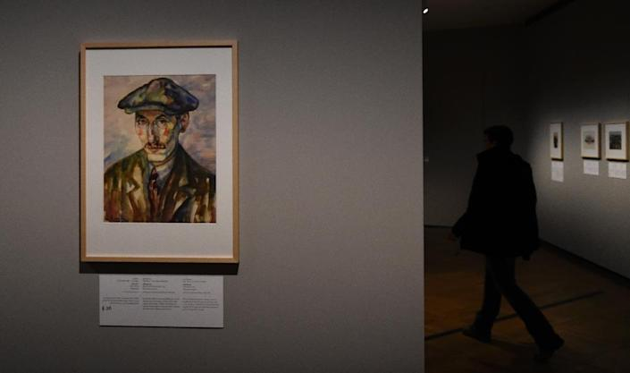 A man is seen among paintings at the exhibition 'Art from the Holocaust -100 Works from the Yad Vashem Collection' during a press preview in Berlin on January 25, 2016 (AFP Photo/Tobias Schwarz)