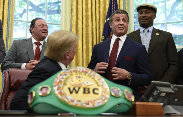 President Donald Trump, second from left, listens as Sylvester Stallone speaks during an event in the Oval Office of the White House in Washington, Thursday, May 24, 2018, where Trump posthumous pardoned Jack Johnson, boxing's first black heavyweight champion. Trump is joined Keith Frankel, left, and former heavyweight champion Lennox Lewis. (AP Photo/Susan Walsh)