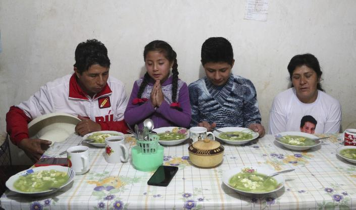 Free Peru party presidential candidate Pedro Castillo, from left, daughter Alondra, son Arnold and wife Lilia Paredes, pray before eating breakfast, in their home in Chugur, Peru, Friday, April 16, 2021. Castillo, a rural teacher, who has proposed rewriting Peru's constitution and deporting all immigrants living in the country illegally who commit crimes, will face rival candidate Keiko Fujimori in the June 6 presidential run-off election. (AP Photo/Martin Mejia)