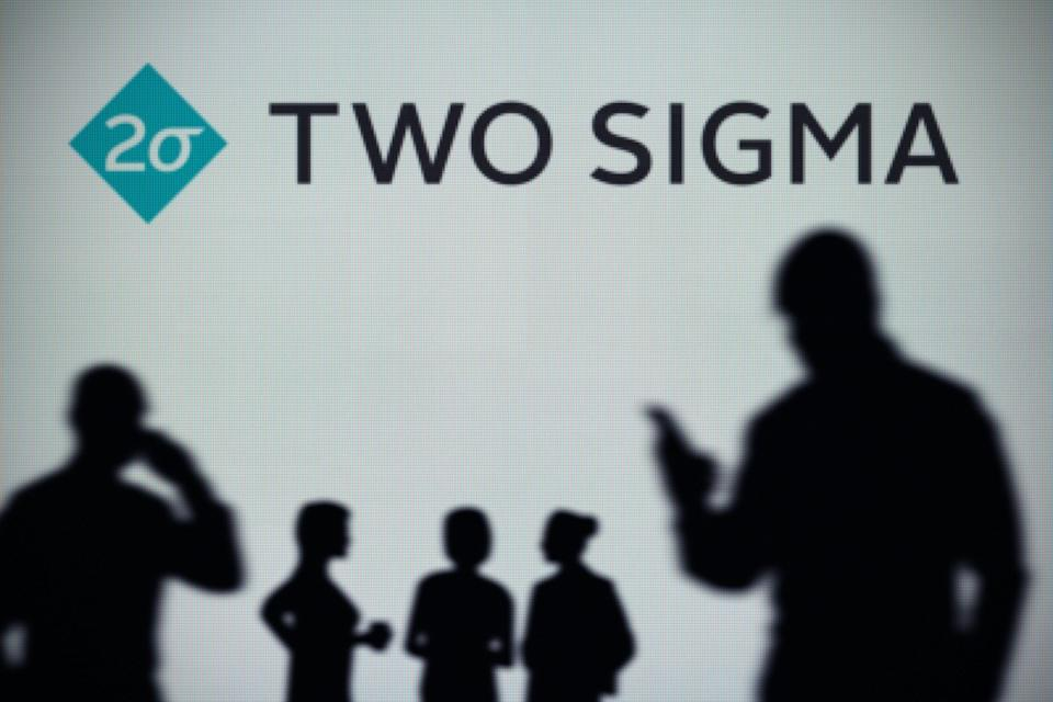 The Two Sigma logo is seen on an LED screen in the background while a silhouetted person uses a smartphone