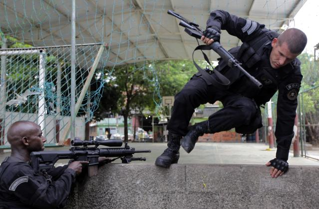 Policemen take position during an operation in the Mare slums complex in Rio de Janeiro