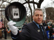 FILE - In this Saturday, March 16, 2002 file photo, firefighter Dan Walker displays a photo of Father Mychal Judge taped inside his hat during the 241st St. Patrick's Day Parade in New York. Judge, the Catholic chaplain of the New York City Fire Department, was killed in the Sept. 11 attacks on the World Trade Center. (AP Photo/Chad Rachman, File)