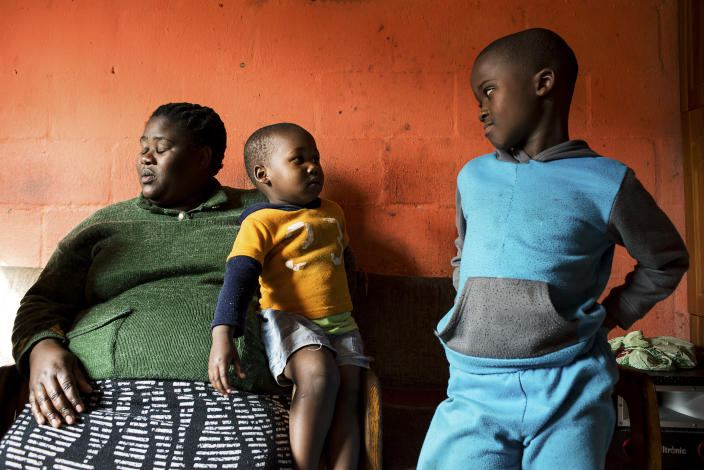 <p>Wendy, a single mother, with her two children in their home. Wendy lives in Langa, the oldest township in the suburbs of Cape Town, and suffers from diabetes caused by obesity. Her diet is mainly made up of fried foods, red meat, and meals purchased at fast food restaurants. Her two children say that their diet consists of chips, fast food dishes, and sweets. (Photograph by Silvia Landi) </p>