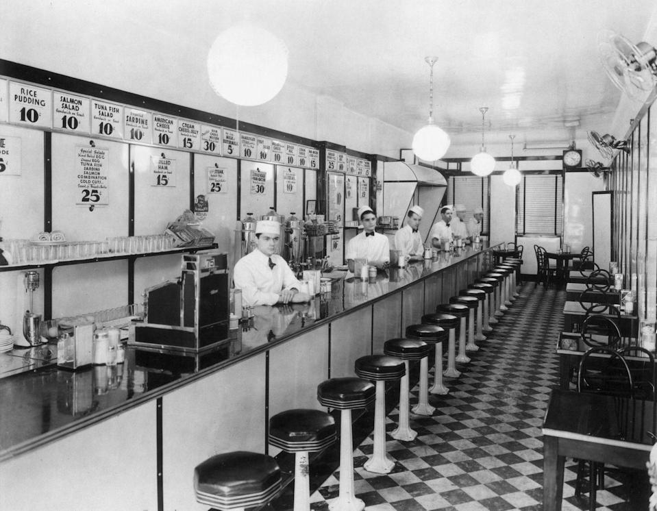"""<p>As the '40s went on, the look of the <a href=""""https://archive.curbed.com/2017/5/30/15716116/restaurants-diners-prefab-historic-preservation"""" rel=""""nofollow noopener"""" target=""""_blank"""" data-ylk=""""slk:diner continued to change"""" class=""""link rapid-noclick-resp"""">diner continued to change</a>. Booths replaced tables, Formica countertops and stainless steel stools became staples, and neon signs were hung outside. </p>"""