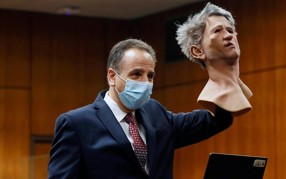 Deputy District Attorney Habib A. Balian holds a rubber latex mask, worn by Robert Durst when police arrested him - Pool Los Angeles Times