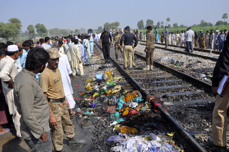 Pakistani soldiers and officials examine a train damaged by the fire in Liaquatpur, Pakistan. Source: AP Photo / Siddique Baluch.