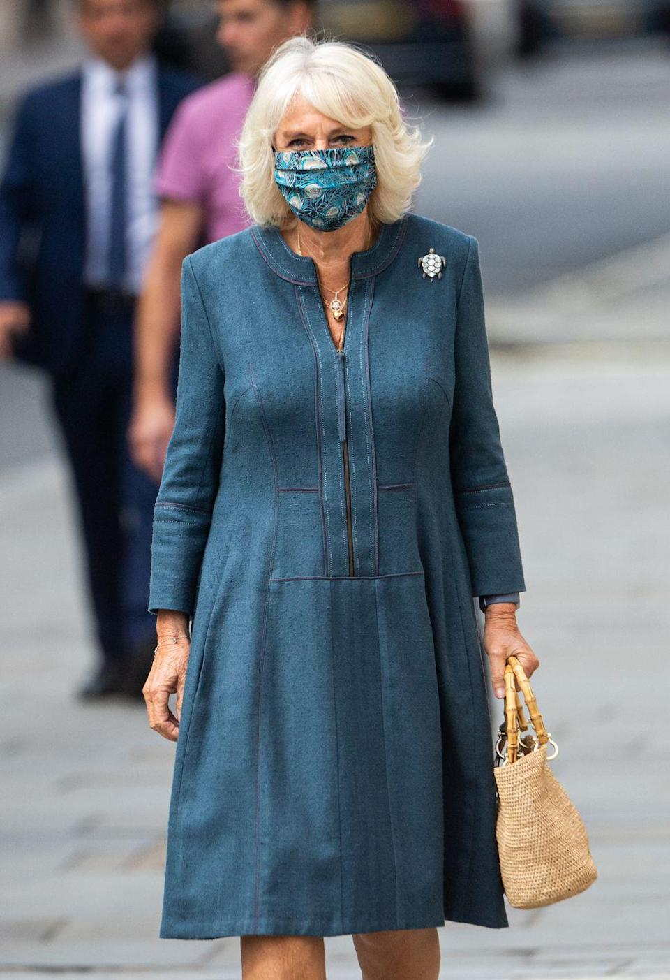 """<p>For her first inside engagement since the coronavirus hit the UK, Camilla paired a blue dress with a turtle-shaped brooch and<a href=""""https://www.townandcountrymag.com/society/tradition/g32616136/queen-elizabeth-princess-charlotte-royal-family-liberty-of-london-print-photos/"""" rel=""""nofollow noopener"""" target=""""_blank"""" data-ylk=""""slk:a Liberty print mask."""" class=""""link rapid-noclick-resp""""> a Liberty print mask.</a></p>"""
