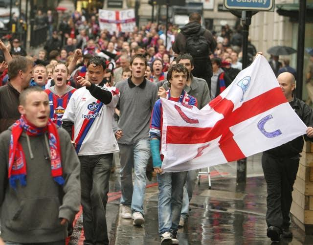 Crystal Palace fans celebrate near London Bridge following an announcement that the club is to be saved from extinction