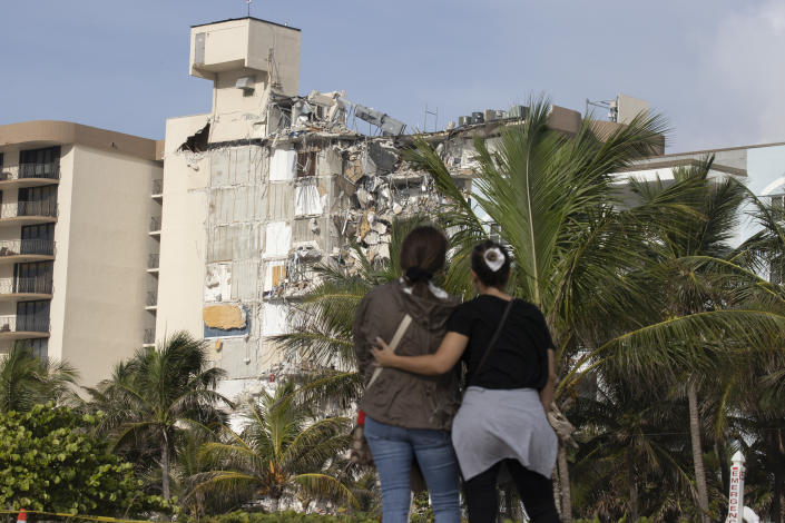 SURFSIDE, FLORIDA - JUNE 25: Maria Fernanda Martinez and Mariana Cordeiro (L-R) look on as search and rescue operations continue at the site of the partially collapsed 12-story Champlain Towers South condo building on June 25, 2021 in Surfside, Florida. Over one hundred people are being reported as missing as search-and-rescue effort continues with rescue crews from across Miami-Dade and Broward counties. (Photo by Joe Raedle/Getty Images)