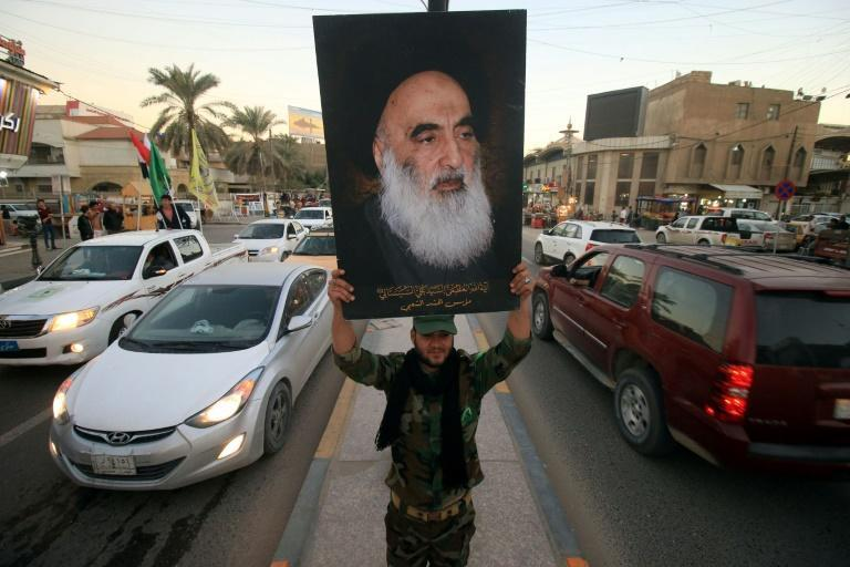 A portrait of Grand Ayatollah Ali Sistani is carried in a Basra street in 2017