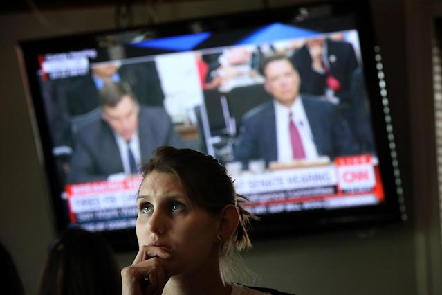 """<p>Leah Thrum joins patrons at Shaw's Tavern to watch former FBI Director James Comey testify before the Senate Intelligence Committee June 8, 2017 in Washington, DC. Shaw's Tavern announced early in the week that In honor of the hearing the bar would host a """"covfefe"""" and offer $5 Russian vodka flavors and $10 """"FBI"""" sandwiches. (Win McNamee/Getty Images) </p>"""