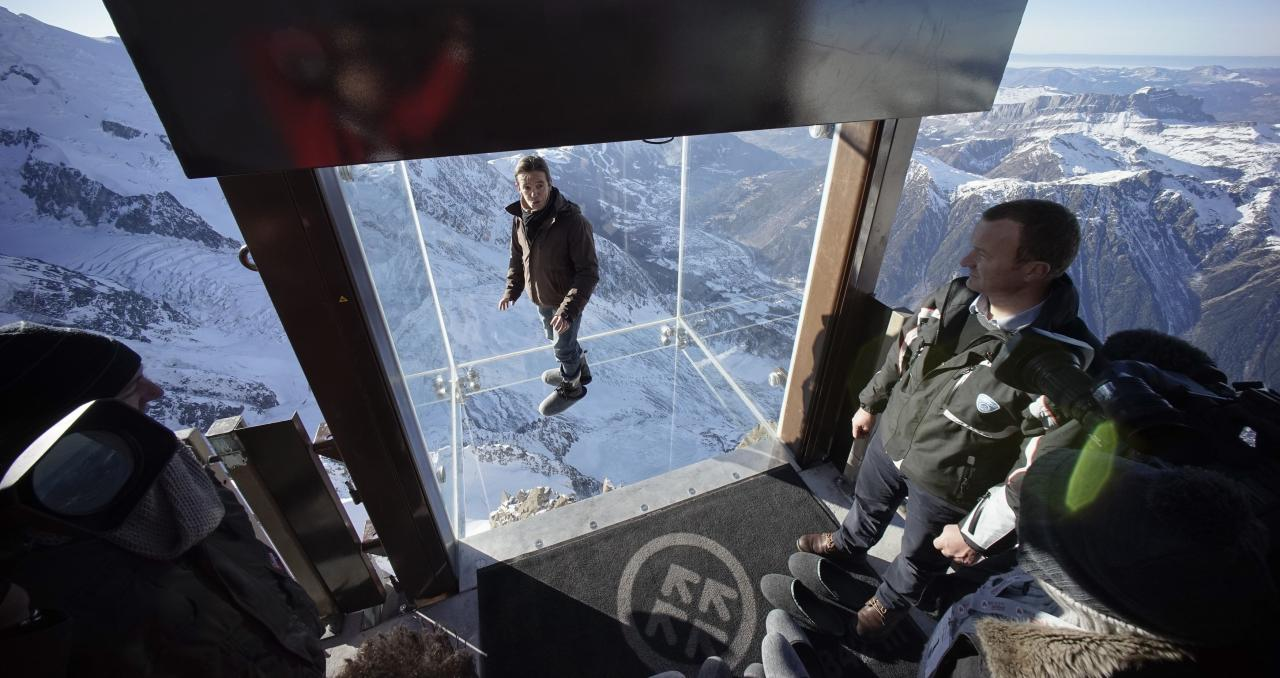 Journalists and employees, wearing slippers to protect the glass floor, stand in the 'Step into the Void' installation during a press visit at the Aiguille du Midi mountain peak above Chamonix, in the French Alps, December 17, 2013. The Chamonix Skywalk is a five-sided glass structure installed on the top terrace of the Aiguille du Midi (3842m), with a 1,000 metre drop below, where visitors can step out from the terrace, giving the visitors the impression of standing in the void. The glass room will open to the public on December 21, 2013. REUTERS/Robert Pratta (FRANCE - Tags: SOCIETY TRAVEL CITYSCAPE)