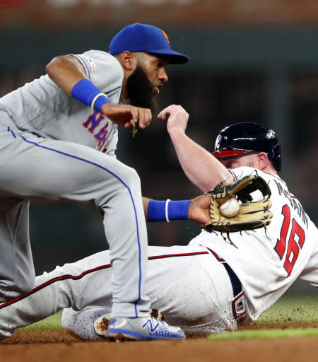 Atlanta Braves' Brian McCann (16) advances to second base on a wild pitch as New York Mets shortstop Amed Rosario handles the late throw during the fifth inning of a baseball game Tuesday, Aug. 13, 2019, in Atlanta. The Braves won 5-3. (AP Photo/John Bazemore)