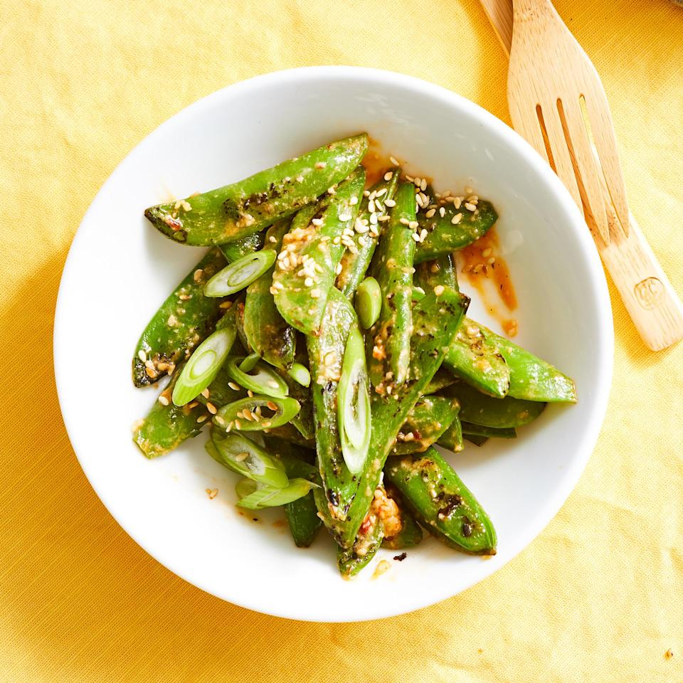 <p>Miso, chile-garlic sauce and vinegar lend serious savory flavor to the compound butter used to coat the charred peas.</p>
