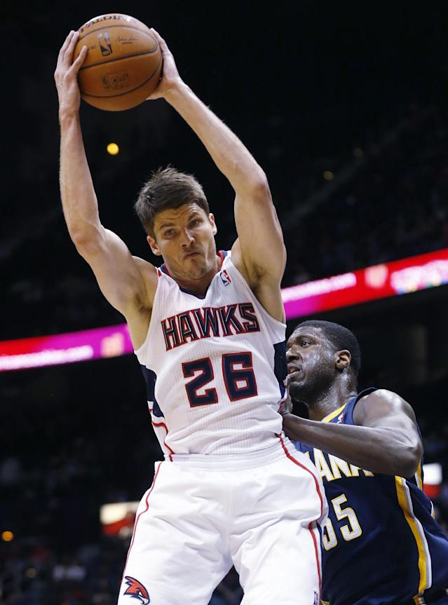 Atlanta Hawks shooting guard Kyle Korver (26) grabs a rebound in front of Indiana Pacers center Roy Hibbert (55) in the first half of an NBA basketball game, Tuesday, Feb. 4, 2014, in Atlanta. (AP Photo/John Bazemore)