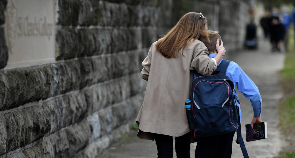 A Sydney schoolboy is comforted by his mother.