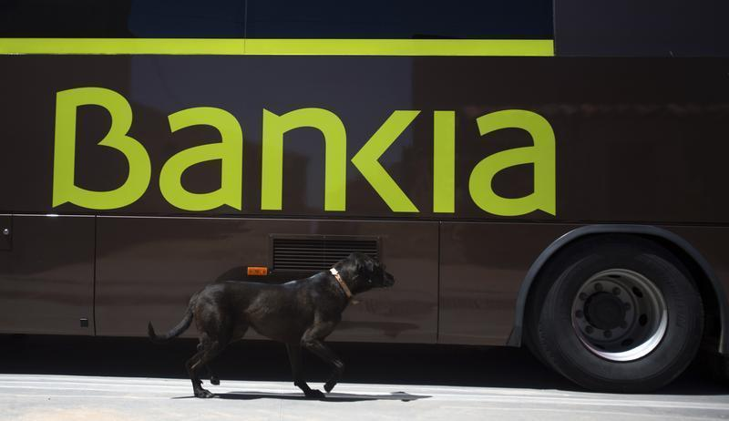A dog walks past a bank bus in the village of Corral de Ayllon in central Spain