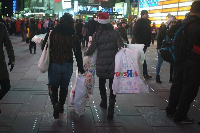Women make their way though Times Square with bags of purchases from Toys R Us in New York