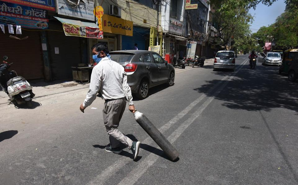 A family member of Covid-19 patient carries an empty cylinder to refill outside the oxygen filling center at Dilshad Garden Area in New Delhi, India.