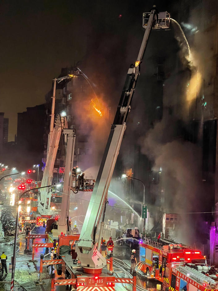 Firefighters battle a building fire in Kaohsiung, in southern Taiwan on Thursday, Oct. 14, 2021. The death toll from a fire in southern Taiwan that engulfed a building overnight has further risen, according to officials Thursday who said dozens more were injured. (AP Photo/Huang Minghsiung)