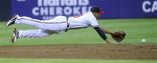 Atlanta Braves shortstop Andrelton Simmons can't get his glove on a ball hit by Arizona Diamondbacks' Miguel Montero during the second inning of a baseball game, Tuesday, June 26, 2012, in Atlanta. (AP Photo/John Amis)