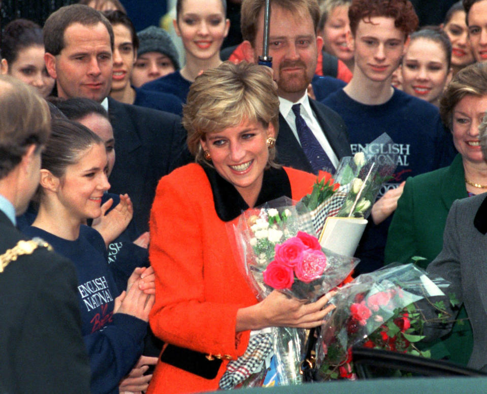 """FILE - This is a Wednesday Dec. 6, 1995 file photo of Diana, the Princess of Wales as she smiles after receiving bouquets of flowers from admirers as she leaves the English National Ballet school opening in London. For someone who began her life in the spotlight as """"Shy Di,"""" Princess Diana became an unlikely, revolutionary during her years in the House of Windsor. She helped modernize the monarchy by making it more personal, changing the way the royal family related to people. By interacting more intimately with the public -- kneeling to the level of children, sitting on edge of a patient's hospital bed, writing personal notes to her fans -- she set an example that has been followed by other royals as the monarchy worked to become more human and remain relevant in the 21st century. (AP Photo/Jacqueline Arzt, File)"""