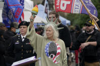 """FILE - In this Wednesday, Jan. 6, 2021 file photo, a person dressed as """"Lady Liberty"""" wears a shirt with the letter Q, referring to QAnon, as protesters take part in a protest at the Capitol in Olympia, Wash., against the counting of electoral votes in Washington, DC, affirming President-elect Joe Biden's victory. Twenty years on, the skepticism and suspicion first revealed by 9/11 conspiracy theories has metastasized, spread by the internet and nurtured by pundits and politicians like Donald Trump. One hoax after another has emerged, each more bizarre than the last: birtherism. Pizzagate. QAnon. (AP Photo/Ted S. Warren, File)"""