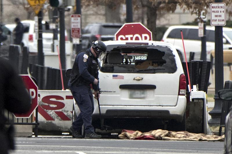 A Secret Service officer checks a white passenger vehicle that struck a security barrier that guards the southwest entrance to the White House: AP