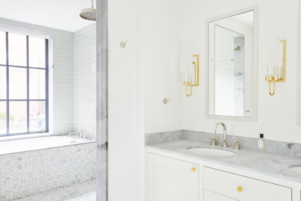 The main bath is equally serene thanks to a subtle white-and-gray color palette. The sconces are by Urban Electric Company, and the hardware is by E.R. Butler & Co.