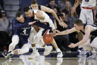 BYU guard Nick Emery (4) and guard McKay Cannon, right, and Gonzaga guard Geno Crandall go after the ball during the first half of an NCAA college basketball game in Spokane, Wash., Saturday, Feb. 23, 2019. (AP Photo/Young Kwak)