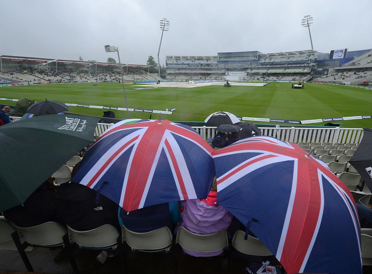 Fans shelter under umbrellas as groundstaff work to dry the pitch prior to the first day of the third cricket Test match between England and the West Indies at Edgbaston in Birmingham, central England, on June 7, 2012. Rain delayed the scheduled start of the third Test between England and the West Indies at Edgbaston on June 7.  AFP PHOTO / ANDREW YATES      RESTRICTED TO EDITORIAL USE. NO ASSOCIATION WITH DIRECT COMPETITOR OF SPONSOR, PARTNER, OR SUPPLIER OF THE ECB        (Photo credit should read ANDREW YATES/AFP/GettyImages)