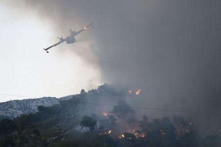 A firefighting plane drops water to extinguish a wildfire in the village of Mravince near Split