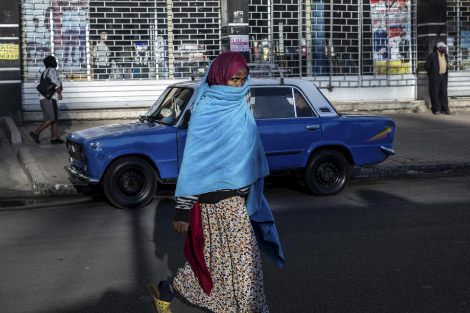 "A woman walks down a street in the capital Addis Ababa, Ethiopia Friday, Nov. 13, 2020. Tensions over the deadly conflict in Ethiopia are spreading well beyond its cut-off northern Tigray region, as the federal government said some 150 suspected ""operatives"" accused of seeking to ""strike fear and terror"" throughout the country had been detained. (AP Photo/Mulugeta Ayene)"