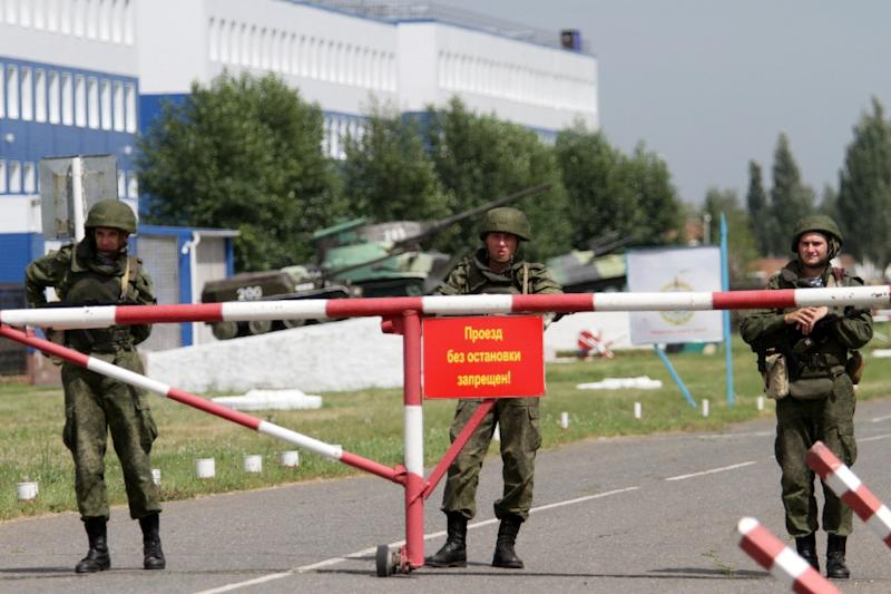 Russian soldiers stand guard at a gate near the destroyed training facility for paratroopers in the village of Svetly, near Omsk, on July 13, 2015 (AFP Photo/Dmitry Feoktistov)