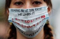Elly Hawkins wearing a face mask bearing slogans poses to a camera during a Black Lives Matter protest following the death in Minneapolis police custody of George Floyd, in Tokyo
