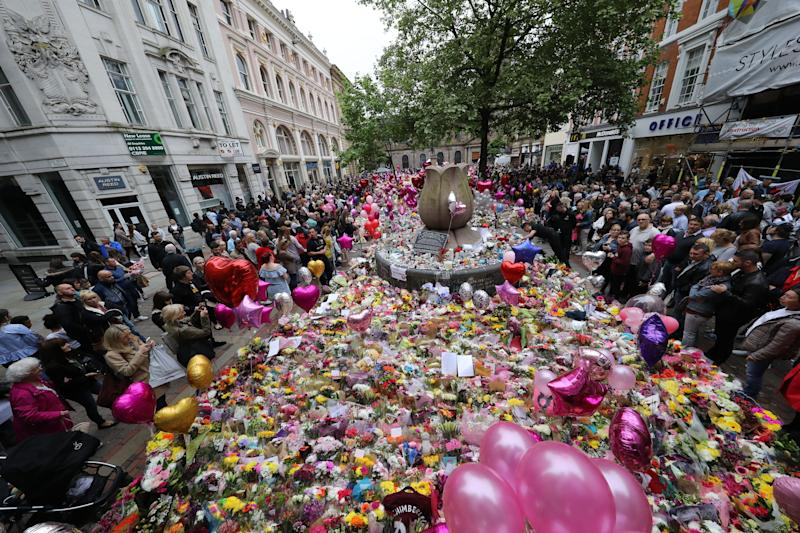 People look at flowers and tributes left in St Ann's Square in Manchester, England, Monday May 29, 2017, exactly a week after the Manchester Arena terror attack took place. Over 20 people were killed in the blast with many more injured. (Owen Humphreys/PA via AP)
