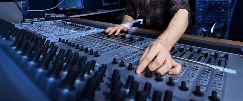 Man using a sound mixing desk in a recording studio.