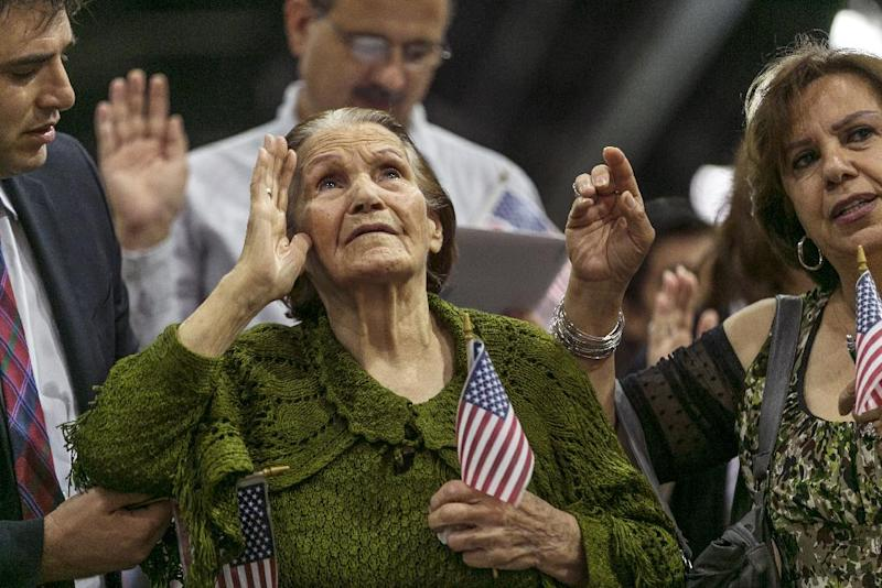 CORRECTS DAUGHTERS FIRST NAME TO ASHKARUEE -New American Khatoun Novasartian Khoykani, a 99-year-old woman from Iran pledges alliance with nearly 7,500 other people becoming U.S. Citizens at the L.A. Convention Center in Los Angeles Friday, July 26, 2013. On Friday, Khoykani became the oldest person this year to join the small group of naturalized citizens over the age of 95. Each year, less than ten people older than 95 become citizens in Los Angeles, according to U.S. Citizenship and Immigration Services. Only 27 people older than 100 have become citizens in the past 50 years. At left, her attorney Peter Hosharian, left, and her daughter, Ashkaruee Khachadurina, right. (AP Photo/Damian Dovarganes)