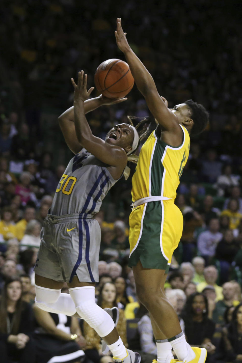 West Virginia guard Madisen Smith, left, attempts a basket while pressured by Baylor guard Moon Ursin, right, in the first half of an NCAA college basketball game, Saturday, Jan. 18, 2020, in Waco, Texas. (AP Photo/Rod Aydelotte)