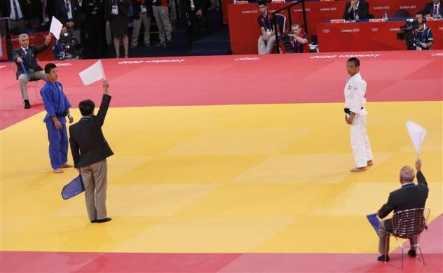 CROWD REVERSES DECISIONS: The referee and judges hold up white flags to indicate Japan's Masashi Ebinuma (white) as the new winner in the men's —66kg quarter— final judo match against South Korea's Cho Jun-Ho (blue) at the London 2012 Olympic Games July 29, 2012.