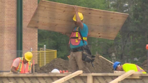 Construction workers at the site for the joint-use building that will be shared by Argyle School and École St. Pius X. The new facility is expected to open in 2023. (CBC - image credit)