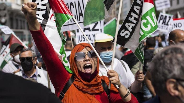 A woman at a protest with arm raised women taking part in a Saharawi freedom march in Madrid, Spain - Friday 18 June 2021