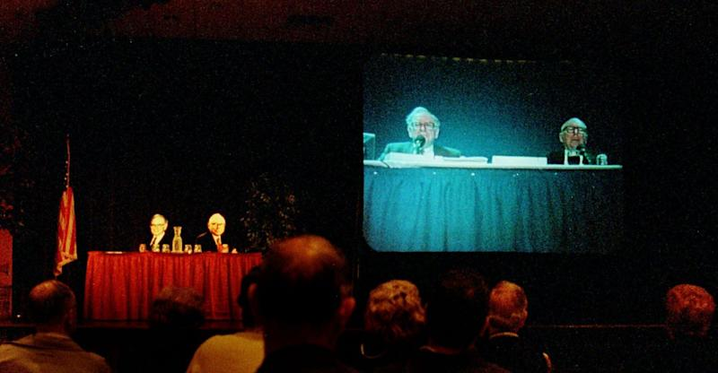 Shareholders of Berkshire Hathaway listen to Warren Buffett, left, and Charlie Munger on closed circut TV at an alternate location with cardboard cutouts at the table shown, as they address questions from sharholders during their annual sharholders meeting Monday May 3, 1999 in Omaha, Neb. (AP Photo/Dave Weaver)