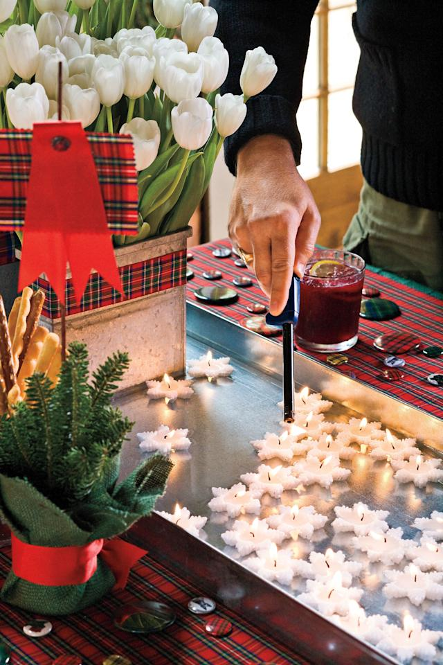 <p>Instead of a traditional table runner, try this Christmas table decoration as an alternative. Place boot trays, or shallow trays, end to end down the full lengthwise center of your dining room table. To prevent accidental leakage, seal the trays with silicon caulk before filling them with water. Buy festive float candles, like the snow-flake shapes we have pictured above, to illuminate your dining room in holiday cheer. We love this unique Christmas decoration idea so much that we want to put a float candle tray in every room. </p>