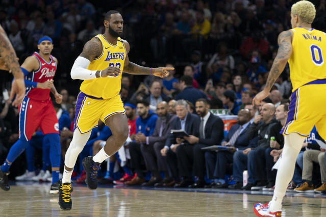 Los Angeles Lakers' LeBron James, center, reacts to his basket moving him to third on the NBA All-time scoring during the second half of an NBA basketball game against the Philadelphia 76ers, Saturday, Jan. 25, 2020, in Philadelphia. LeBron James passes Kobe Bryant for third on the NBA all-time scoring. (AP Photo/Chris Szagola)