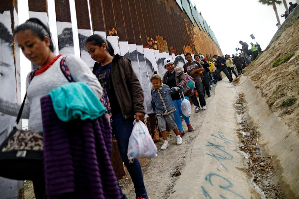 Members ofthecaravan that traveled across Mexicowalk next to the border fence.