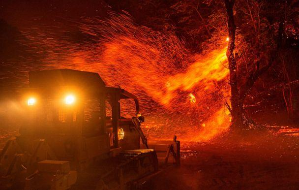 PHOTO: Embers fly off a tree as a bulldozer is prepared to help fight fire during the Kincade fire near Geyserville, California on October 24, 2019. (Josh Edelson/AFP via Getty Images)
