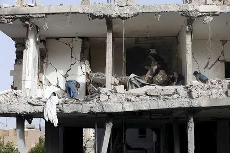 People salvage furniture from the rubble of a house destroyed by an air strike in Sanaa. REUTERS/Khaled Abdullah