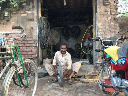 A man fixes a motorcycle tyres at his workshop in the town of Rabwah