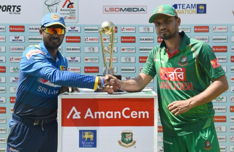 Sri Lanka captain Upul Tharanga (L) and Bangladesh captain Mashrafe Mortaza pose with the series trophy ahead of the first ODI at The Rangiri Dambulla International Cricket Stadium in Dambulla on March 25, 2017